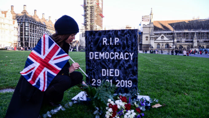 Protestor Sits at Fake Grave for Democracy