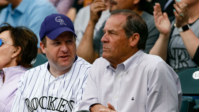 Colorado Gov. Jared Polis, left, who signed sports betting legislation this summer, sits with Rockies ower Dick Monfort during a Rockies game against the San Diego Padres at Coors Field in June.