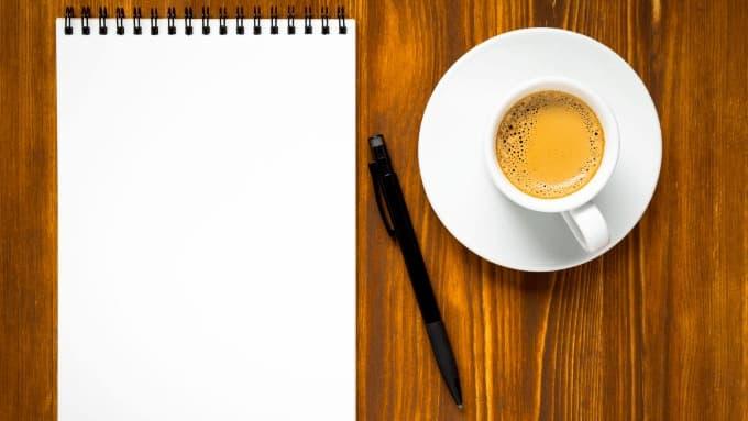 Hand schreibt in ein Notizbuch