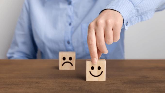 Hand wählt Holzwürfel mit lächelndem Gesicht